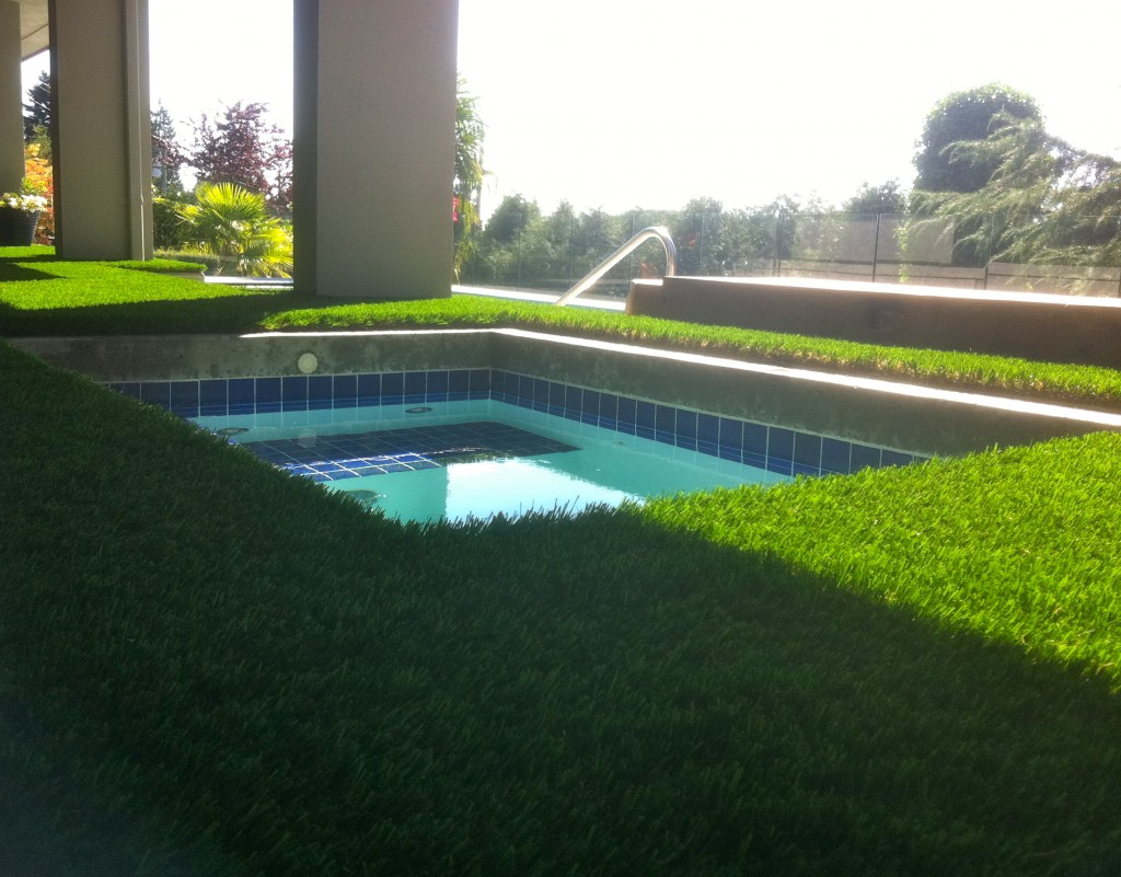 Synthetic grass around hot tub helps eliminate dirt and gravel in the water.